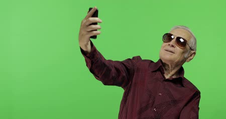 yedek : Senior man tourist in sunglasses make a photo on a smartphone. Selfie. Handsome old man on chroma key background. Elderly grandfather in maroon shirt. Green screen background