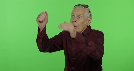 étonnement : Senior man something emotionally shows amazement, surprise. Handsome old man on chroma key background. Elderly grandfather in maroon shirt. Place for your logo or text. Green screen background