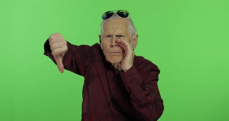 displeasure : Senior man something giving thumb down. Handsome old man showing displeasure gesture on chroma key background. Elderly grandfather in maroon shirt. Green screen background Stock Footage