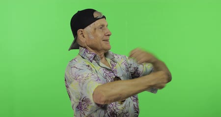 гавайский : Senior man tourist dances. Handsome old man on chroma key background. Elderly grandfather in colorful shirt. Place for your logo or text. Green screen background Стоковые видеозаписи