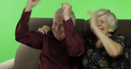 társ : Senior aged man and woman sitting together on a sofa and watching TV and laughing. Chroma key background. Concept of a happy family in old age. Green screen background Stock mozgókép