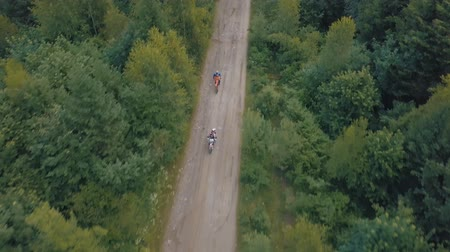 motorcross : Extreme motorcyclists rides on road in the forest. Motocross. Motosport. Stock footage of motorcycle. Aerial view