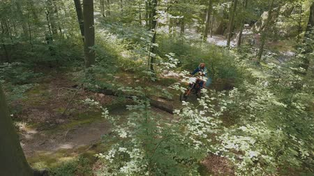 giostre : Extreme motorcyclist rides on the forest roads. Mountain hills. Motocross. Motosport. Stock footage of motorcycle. Aerial view Filmati Stock