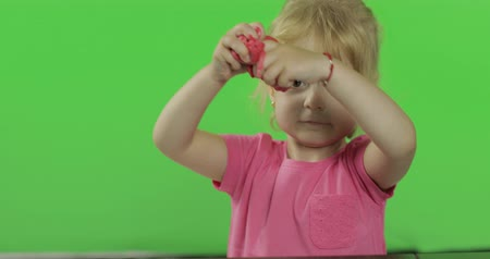 plastilina : Happy little girl plays with plasticine on chroma key background. Child rolls plasticine with her hands, development of fine motor skills of hands. Green screen