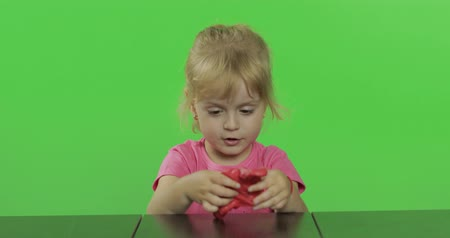 plastelíny : Happy little girl plays with plasticine on chroma key background. Child rolls plasticine with her hands, development of fine motor skills of hands. Green screen