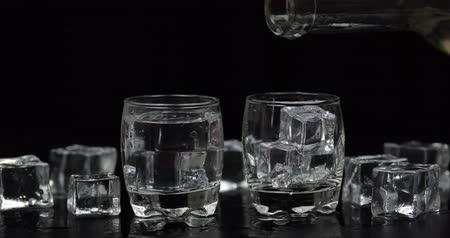 テキーラ : Pouring up two shots of vodka from a bottle into drinking glass against black background with ice cubes. Pour of alcohol drink vodka tequila 動画素材