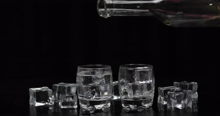sterke drank : Pouring up two shots of vodka from a bottle into drinking glass against black background with ice cubes. Pour of alcohol drink vodka tequila Stockvideo