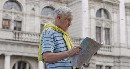 tied : Senior male tourist exploring town with a map in hands and looking for the route while traveling in Lviv, Ukraine. A man in t-shirt and sweater that is tied around his neck. Vacation concept Stock Footage