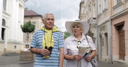 binocolo : Senior two male and female tourists walking in town with a map in hands and looking for the route while traveling in Lviv, Ukraine. Elegant woman in hat. A man with binoculars. Vacation concept