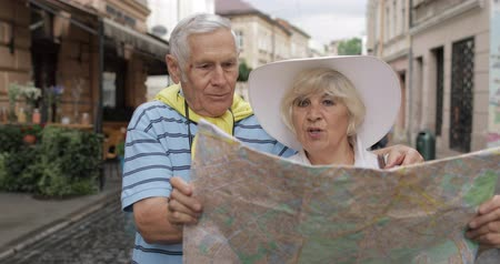 binocolo : Senior two male and female tourists standing in town with a map in hands and looking for the route while traveling in Lviv, Ukraine. Elegant woman in hat. A man with binoculars. Vacation concept Filmati Stock