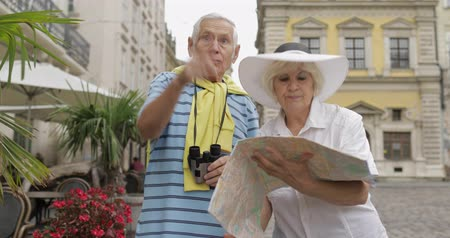 binocolo : Senior two male and female tourists standing in town with a map in hands and having discussion about planning a tourist route while traveling in Lviv, Ukraine. Vacation concept