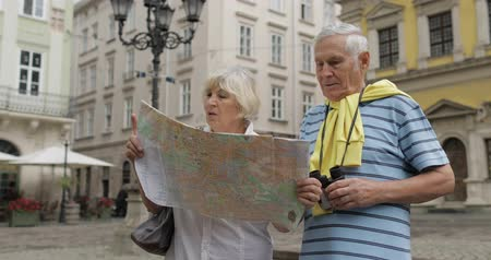 binocular : Senior two male and female tourists walking in town with a map in hands and looking for the route while traveling in Lviv, Ukraine. Elegant woman with bag. A man with binoculars. Vacation concept Stock Footage