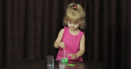 goop : Child having fun making green slime. Mixes ingredients. Kid playing with hand made toy slime. Funny kid girl. Oddly satisfying blue slime for pure fun and stress relief. Dark background