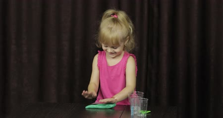 balçık : Child having fun making green slime. Kid playing with hand made toy slime. Funny kid girl. Relax and Satisfaction. Oddly satisfying blue slime for pure fun and stress relief. Dark background