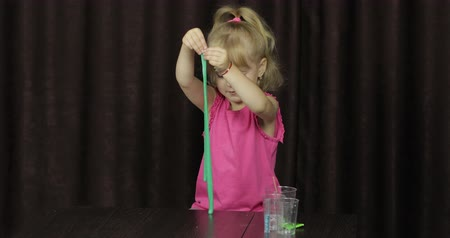 goop : Child having fun making green slime. Kid playing with hand made toy slime. Funny kid girl. Relax and Satisfaction. Oddly satisfying blue slime for pure fun and stress relief. Dark background