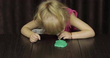 goop : Child having fun making green slime. Kid playing with hand made toy slime. Funny kid girl. Blowing bubble via the drinking straw. Oddly satisfying blue slime for pure fun and stress relief