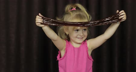 goop : Child having fun making brown slime. Kid playing with hand made toy slime. Funny kid girl. Relax and Satisfaction. Oddly satisfying blue slime for pure fun and stress relief. Dark background