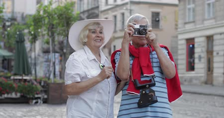 Senior two male and female tourists standing in town center while traveling in Lviv, Ukraine. Elegant woman in hat. A man with photo camera makes a photo. Vacation concept