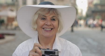 stary : Senior female tourist exploring town and makes a photo with retro photo camera while traveling in Lviv, Ukraine. Elegant woman in hat. Vacation concept