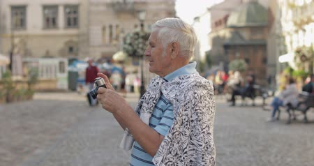 lviv : Senior male tourist exploring town and makes a photo with retro photo camera while traveling in Lviv, Ukraine. T-shirt and sweater in his neck. Vacation concept Stock Footage