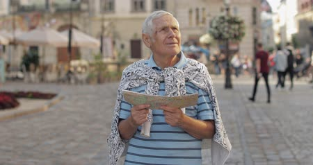 lviv : Senior male tourist exploring town center with a map in hands and looking for the route while traveling in Lviv, Ukraine. Smiling. T-shirt and sweater in his neck. Vacation concept