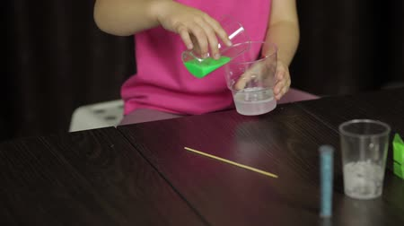 goop : Child hands making green slime. Mixes ingredients. Kid playing with hand made toy slime. Funny kid girl. Oddly satisfying blue slime for pure fun and stress relief. Dark background