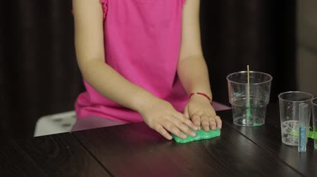 goop : Child hands having fun with green slime. Kid playing with hand made toy slime. Funny kid girl. Relax and Satisfaction. Oddly satisfying blue slime for pure fun and stress relief. Dark background