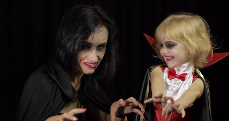 vampiro : Woman and child dracula making faces. Little girl with her mother. Halloween make-up. Vampire kid with blood on her face. Happy Halloween holiday horror concept. Friday 13th theme