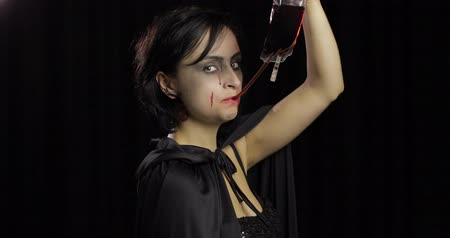 boszorkány : Vampire Halloween woman portrait. Beauty sexy Vampire girl with dripping blood on her mouth. Vampire makeup. Fashion Art design. Attractive model girl in Halloween costume Stock mozgókép
