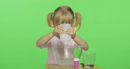 goop : Child having fun making slime. Pour the glue. Kid playing with hand made toy slime. Funny kid girl. Oddly satisfying slime for pure fun and stress relief. Dark background
