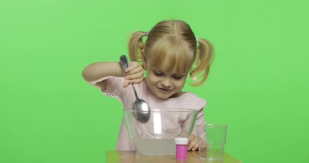 goop : Child having fun making slime. Mixes ingredients. Kid playing with hand made toy slime. Funny kid girl. Oddly satisfying slime for pure fun and stress relief. Dark background