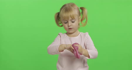 szorítás : Child having fun making ping slime. Kid playing with hand made toy slime. Funny kid girl. Relax and Satisfaction. Oddly satisfying pink slime for pure fun and stress relief. Green screen. Chroma Key
