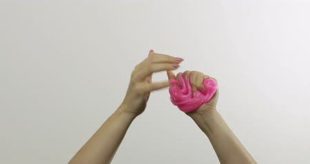 goop : Woman hands playing with oddly satisfying pink slime on white background. Sticky gooey substance. Relax and inexplicably satisfying. Super viral trend on social media for antistress things