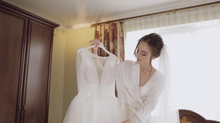camisola : Beautiful and lovely bride in night gown and veil with wedding dress. Pretty and well-groomed woman in nightdress. Wedding morning. Slow motion