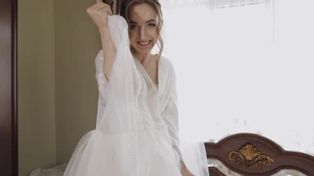 preparált : Beautiful and lovely bride in night gown and veil with wedding dress. Pretty and well-groomed woman in nightdress. Wedding morning. Slow motion