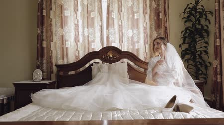 camisola : Beautiful and lovely bride in night gown sitting on bed and drinking champagne. Pretty and well-groomed woman in nightdress. Wedding morning. Slow motion Vídeos
