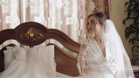 preparált : Beautiful and lovely bride in night gown sitting on bed and drinking champagne. Pretty and well-groomed woman in nightdress. Wedding morning. Slow motion Stock mozgókép