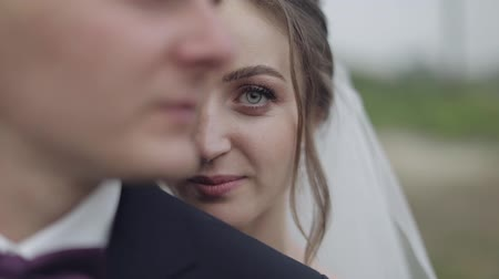 nowożeńcy : Lovely young caucasian bride and groom. Wedding couple. Happy family. Newlyweds. Bride looks at camera. Man and woman in love. Slow motion