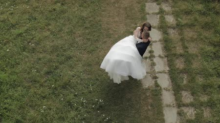 Lovely young caucasian bride and groom in the park. Groom holds bride in his hands. Wedding couple. Happy family. Newlyweds. Man and woman in love. View from top. Slow motion