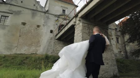 Lovely young caucasian bride and groom in the park near old castle wall. Groom holds bride in his hands. Wedding couple. Happy family. Newlyweds. Man and woman in love. Slow motion