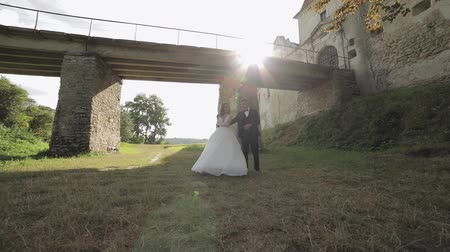 невеста : Lovely young caucasian bride and groom dancing in the park near old castle bridge. Wedding couple. Happy family. Newlyweds. Man and woman in love. Slow motion
