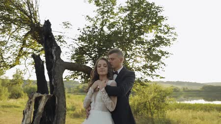 véu : Lovely young caucasian bride and groom in the park near lake. Wedding couple hugging. Happy family. Newlyweds. Man and woman in love. Slow motion Vídeos