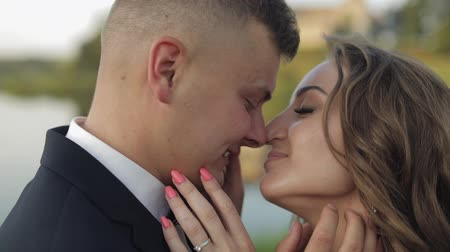 závoj : Lovely young caucasian bride and groom in the park near lake. Wedding couple. Happy family. Newlyweds. Man and woman in love. Slow motion