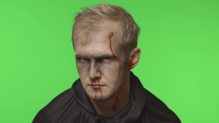 vampiro : Executioner Halloween man portrait. Guy with dripping blood on his face. Executioner, headman makeup. Fashion art design. Attractive model in Halloween costume. Chroma key background