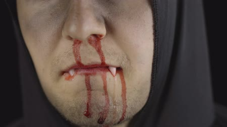 vampiro : Vampire Halloween man portrait close-up. Guy with dripping blood on his face. Executioner, Vampire makeup. Fashion art design. Attractive model in Halloween costume. Dark black background Stock Footage