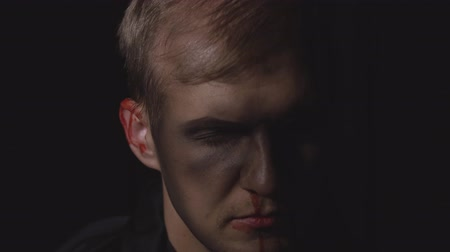 matança : Halloween man portrait with head injury. Guy with dripping blood on his face. Executioner, Vampire makeup. Fashion art design. Attractive model in Halloween costume. Dark black background Stock Footage
