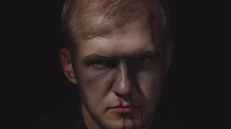 vampiro : Halloween man portrait with head injury. Guy with dripping blood on his face. Executioner, Vampire makeup. Fashion art design. Attractive model in Halloween costume. Dark black background Stock Footage