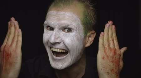 fobi : Clown Halloween man portrait. Close-up of an crazy, evil clowns face. White face makeup. Green hair. Scary laugh. Attractive model in Halloween costume. Dark background