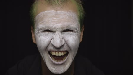 tréfacsináló : Clown Halloween man portrait. Close-up of an crazy, evil clowns face. White face makeup. Green hair. Scary laugh. Attractive model in Halloween costume. Dark background