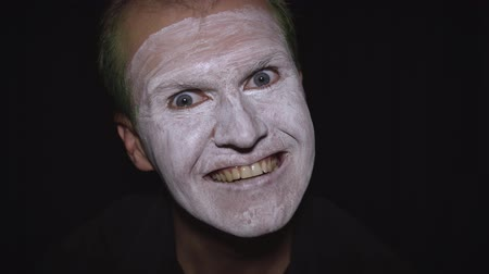 уродливый : Clown Halloween man portrait. Close-up of an crazy, evil clowns face. White face makeup. Green hair. Scary laugh. Attractive model in Halloween costume. Dark background